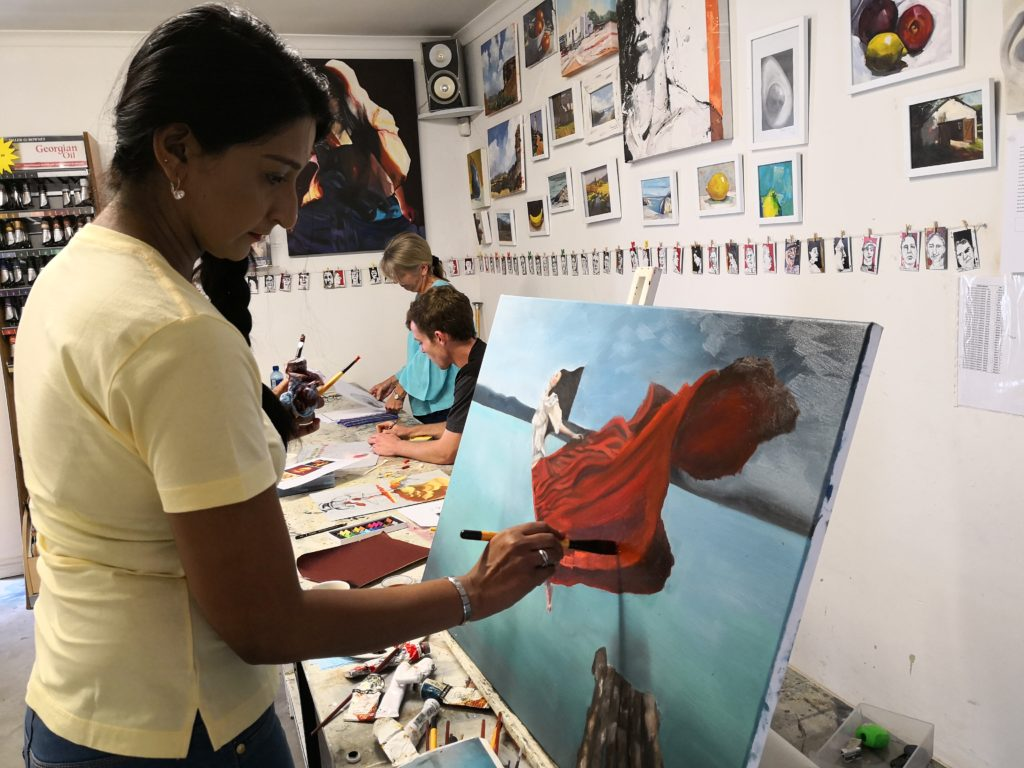 artist in studio painting about Ajay's